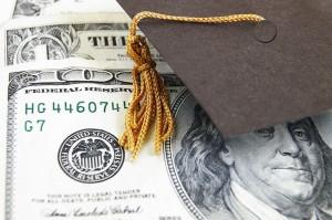 13044485 - mini graduation cap on money