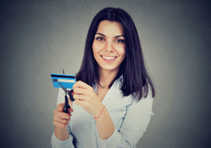 Happy woman cutting in half her credit card with scissors isolated on gray background