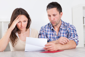 24284604 - portrait of a worried young couple looking at paper