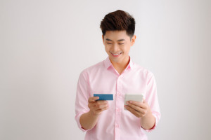 Male hands holding credit card and using smart phone. Online shopping concept